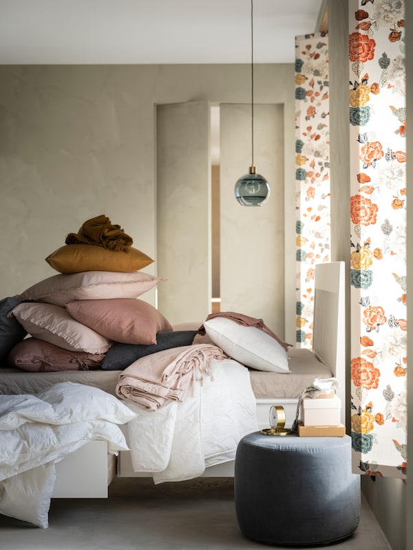 An IDANÄS bed with storage, with cushions, pillows and bedding piled on top and in a storage drawer, stands in a bedroom.