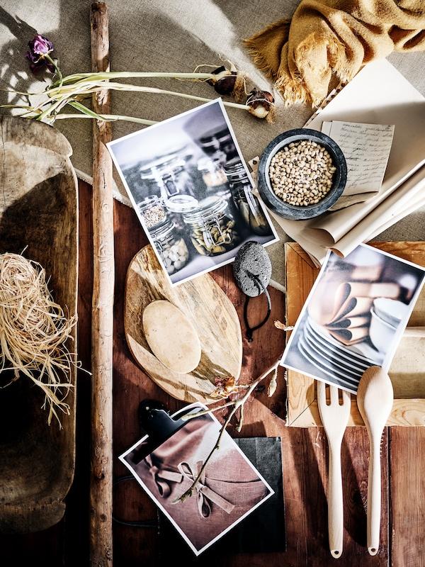 Une table en bois rustique sur laquelle se trouvent des fleurs séchées, des photos, de la paille, un bol, une cuillère en bois, une fourchette et une planche à découper.