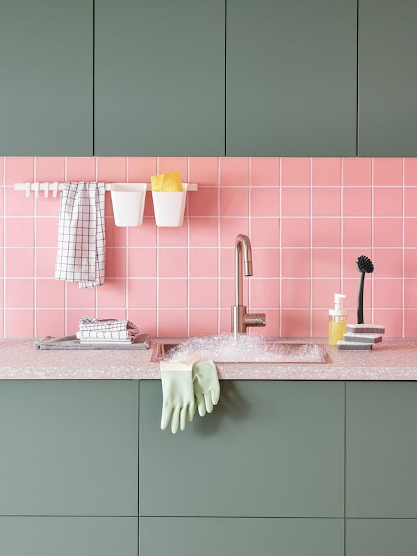 Un espace de cuisine avec des armoires vertes, un dosseret rose, des accessoires pour laver la vaisselle sur le comptoir et un évier rempli de mousse.