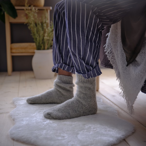 Zwei Beine in einer gestreiften Pyjamahose sitzen an einer Bettkante. Die Füße stehen auf einem weißen TOFTLUND Teppich.