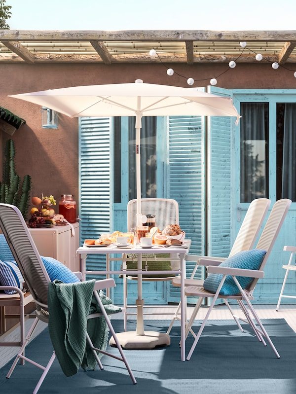 A sunny patio with terracotta walls, blue doors, a white table with a parasol, and white outdoor chairs with blue cushions.