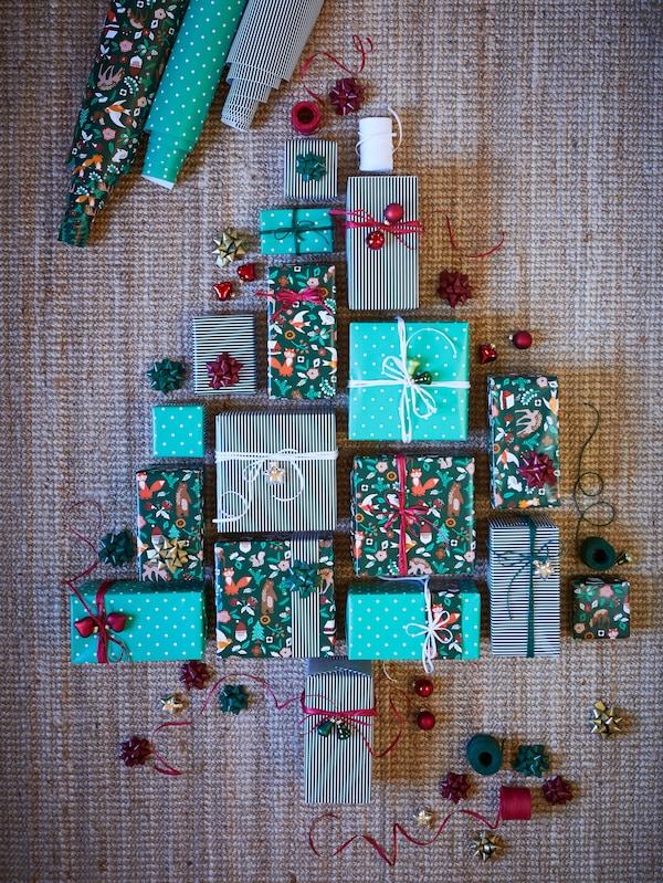 A VINTER 2021 zöld ajándékcsomagolásba csomagolt ajándékok a padlón karácsonyfa alakban elrendezve, szalagokkal díszítve.