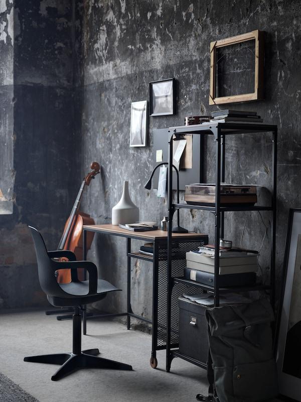 Un espace de travail compact composé d'une table pour ordinateur portable FJÄLLBO noire, d'une étagère FJÄLLBO et d'une chaise pivotante ODGER anthracite.
