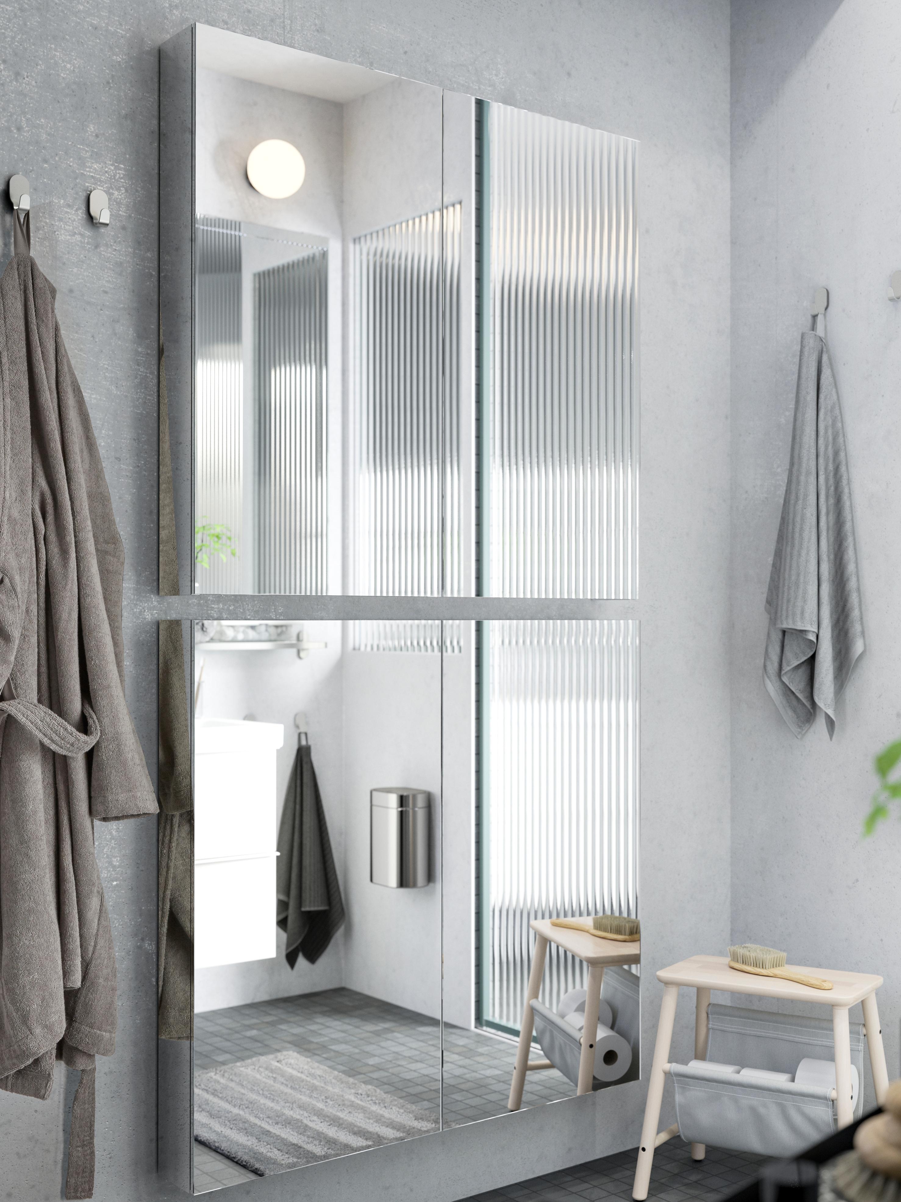 Dva GODMORGON elementa s ogledalima, svaki s dvoja vrata, kupaonica koja se vidi u odrazu ogledala, ručnik koji visi i stolica.
