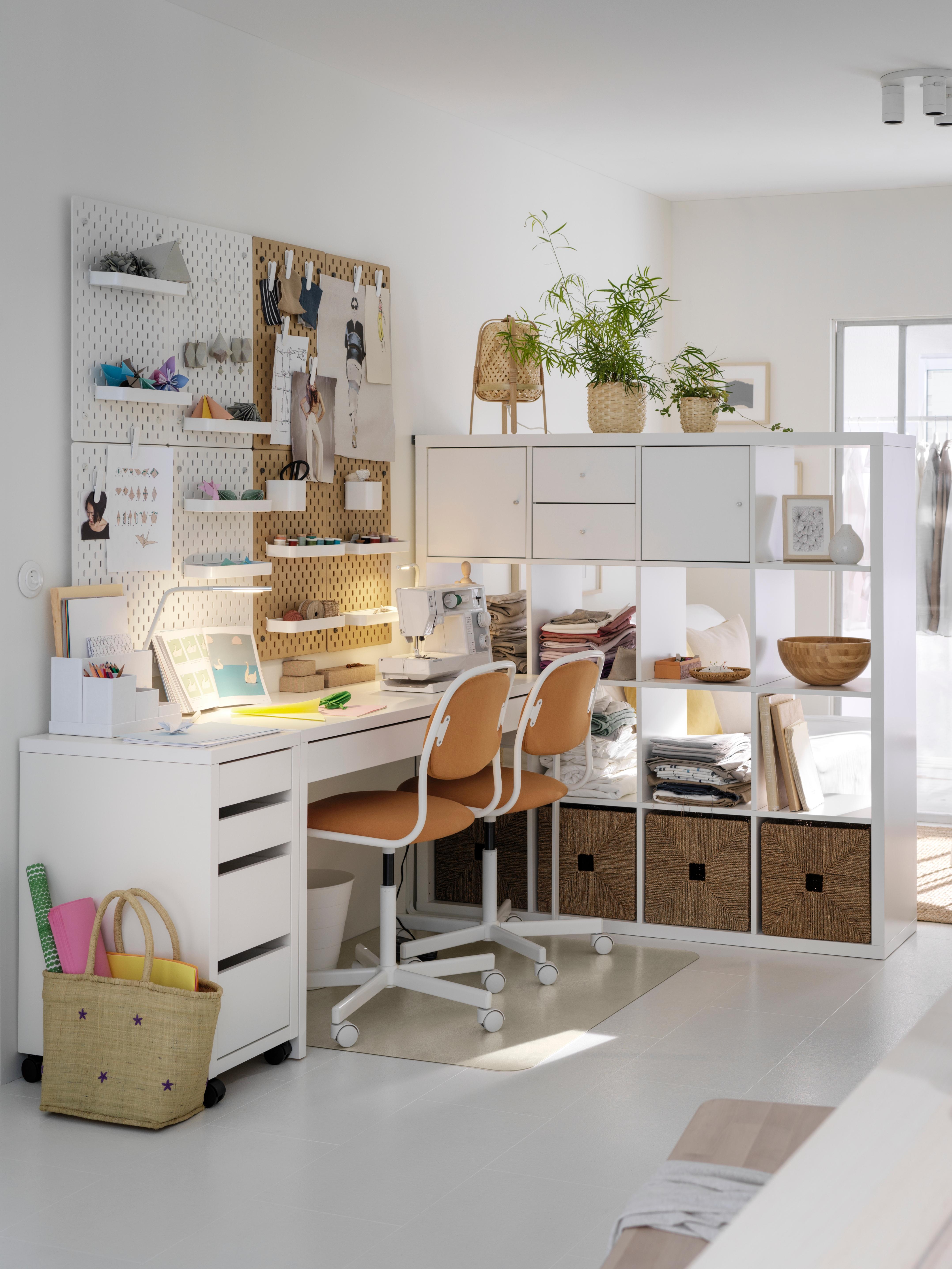 Белый письменный стол MICKE МИККЕ расположен между подходящей к нему тумбой с ящиками на колесах и стеллажом, разделяющим комнату. Возле письменного стола стоят два стула.