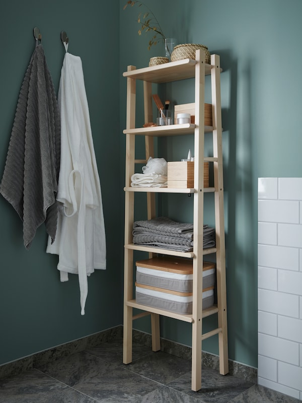 A bathroom with turquoise walls. Two towels are hanging from hooks and a shelving unit in birch is storing bath accessories.