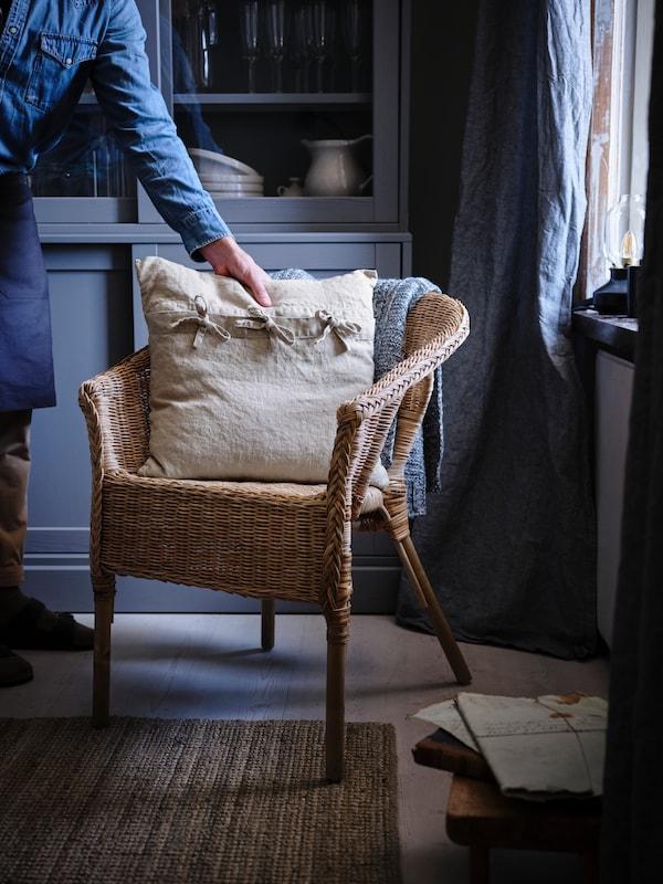 Een AGEN rotanfauteuil staat naast een raam in een kamer met een blauwe inrichting. Iemand legt een kussen met AINA kussenovertrek op het zitgedeelte van de stoel, naast een blauwe plaid.