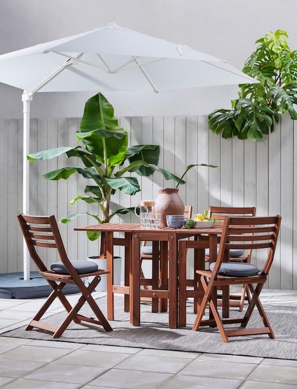 En kvinna som dukar upp för en måltid utomhus i en lummig trädgård på ett mörkbrunt bord med stolar runtomkring.