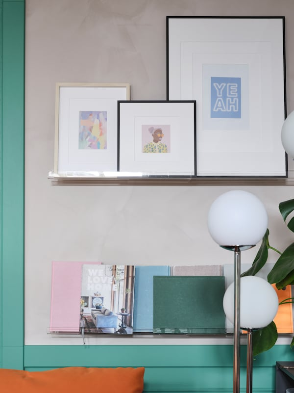 Framed art and posters, books and pastel-colored notebooks are displayed on wall-mounted transparent picture ledges.