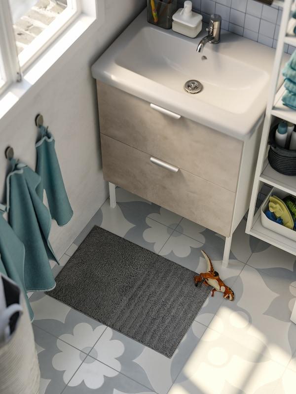 Grå badrumsmatta, intill ligger en leksaksdinosaurie, ljusblå handdukar hänger på krokar på väggen, vitt tvättställ.