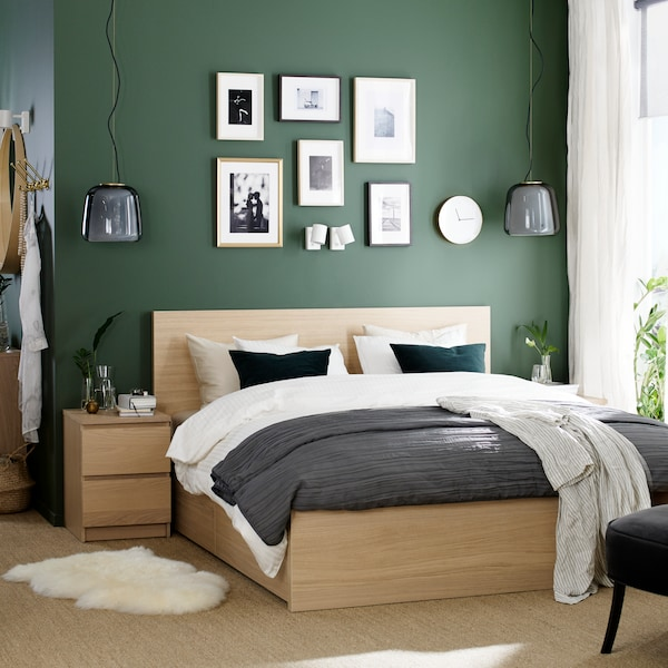 A bedroom with light wood MALM furniture, white and grey bedding, and a gallery of pictures hung on a green-painted wall.