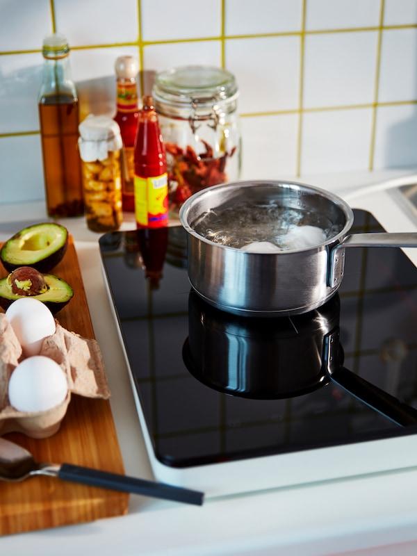 VARDAGEN stekpanna av kolstål i svart med stekt svamp, bredvid en skål med salt och en tallrik med rå svamp.