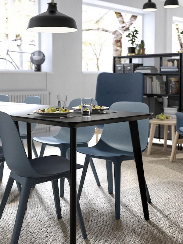 丸みのあるODGER/オドゲル チェアと、ブラックのLISABO/リーサボーの長方形のダイニングテーブルが設置された、オープンな休憩・食事スペース。