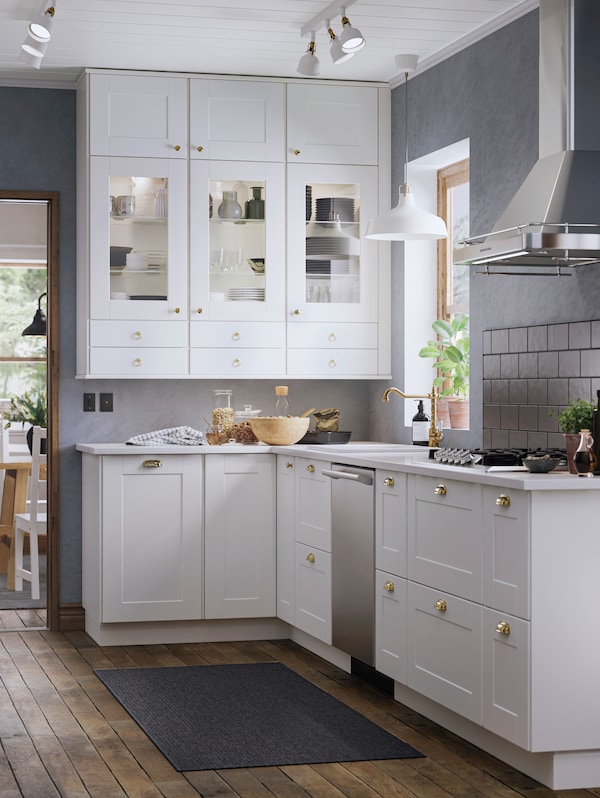 A farm style kitchen with GRIMSLÖV fronts in off-white, brass-coloured knobs and handles and a RANARP pendant lamp.