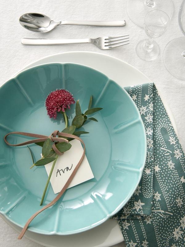 STRIMMIG turkos tallrik på ett uppdukat bord.