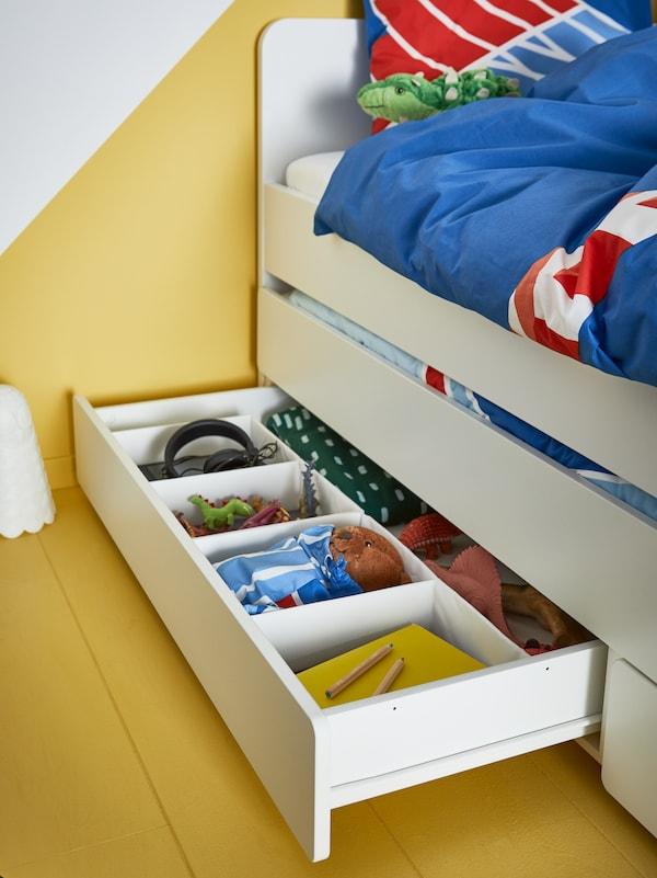 Hvid seng til børn med opbevaring nedenunder. I skuffen er tegneudstyr, legetøj, sengetøj og høretelefoner ordnet i kasser.