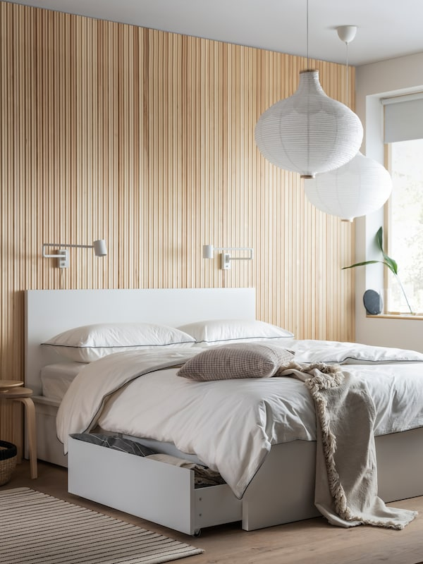 A TUFJORD bed covered with TRUBBTÅG bed linen in a bedroom that has stripped walls and door, with a stool beside it.