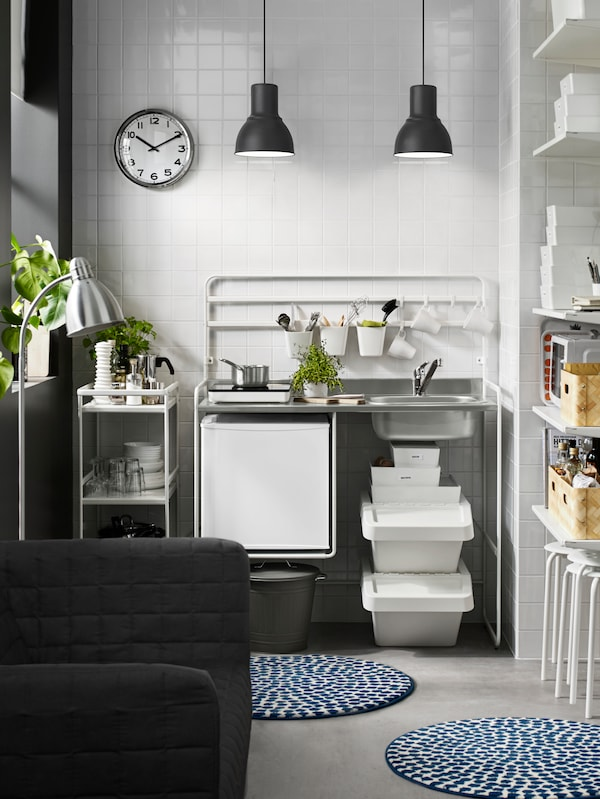 A sun drenched SUNNERSTA mini-kitchen and cart stacked with plates, glasses and condiments, against a white tiled wall.