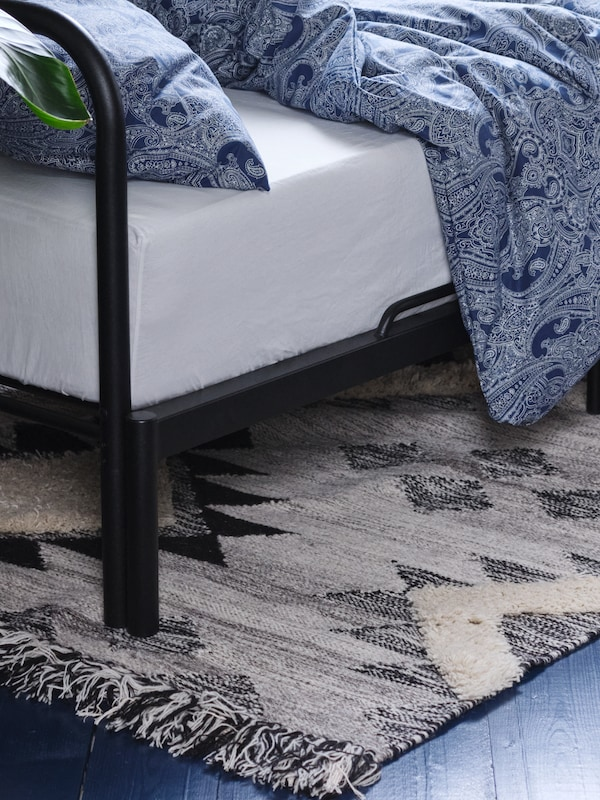 Part of a FYRESDAL day-bed with JÄTTEVALLMO bed linen which is standing on a grey black TANNISBY flatwoven rug.