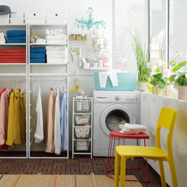 A laundry room with towels and clothes on a JONAXEL white shelving unit and a washing machine next to it.