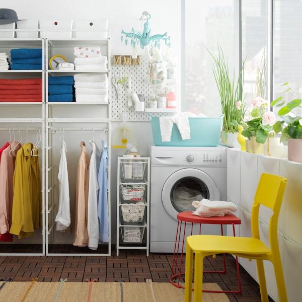 Mosókonyha, törölközőkkel és ruhákkal a JONAXEL fehér polcokon, ami mellett egy mosógép áll.
