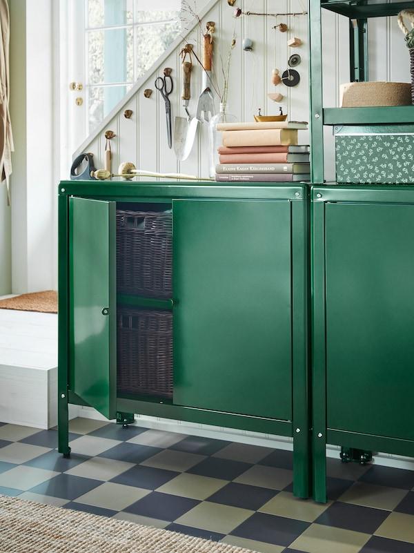 Hai ferramentas de xardín colgadas de ganchos ao lado das escaleiras, detrás duns armarios KOLBJÖRN verdes con libros e unha caixa enriba.