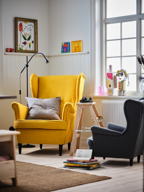 A living room corner with a yellow STRANDMON wing chair and a grey STRANDMON children's armchair.
