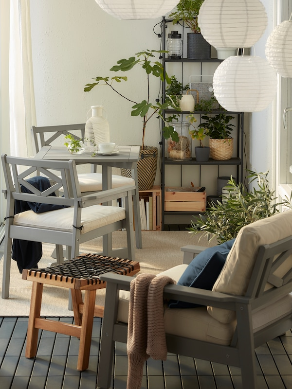 A closed balcony with grey BONDHOLMEN furniture, round pendant lamps, a beige rug, white curtains and lots of plants.