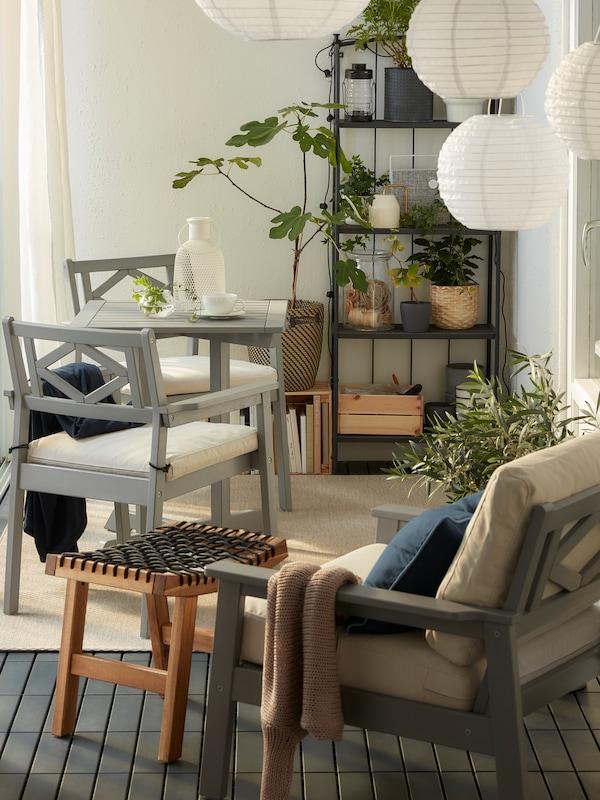 Balcon fermé avec mobilier gris BONDHOLMEN, suspensions rondes, tapis beige, rideaux blancs et nombreuses plantes.