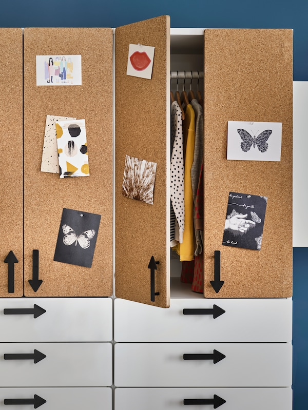 Two SMÅSTAD wardrobes with white drawers, cork doors and arrow-shaped handles stand next to each other. One has an open door.
