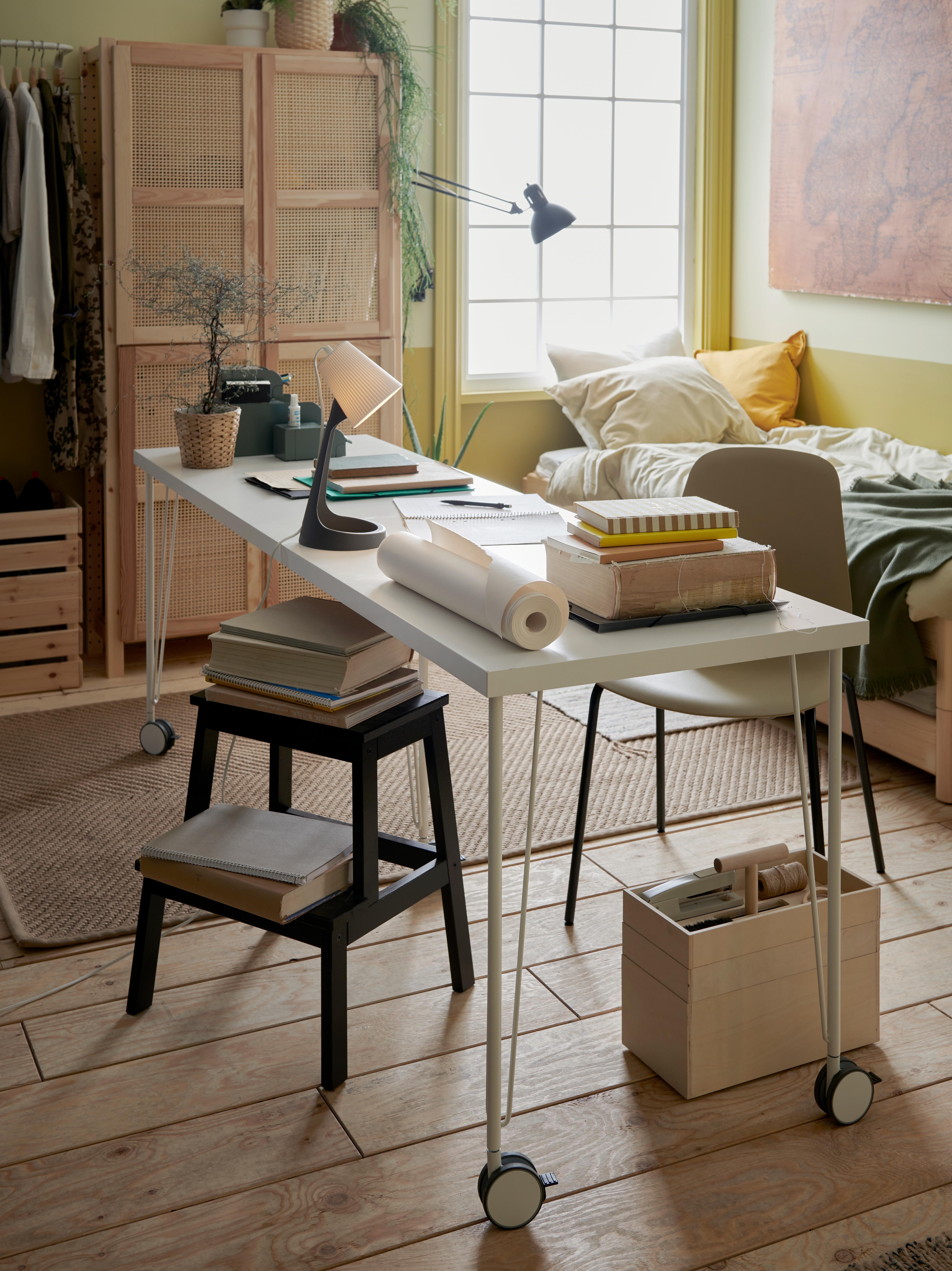Białe biurko na kółkach ustawione na środku przyjemnie urządzonego pokoju studenckiego z trzypoziomową drewnianą skrzynką na podłodze.