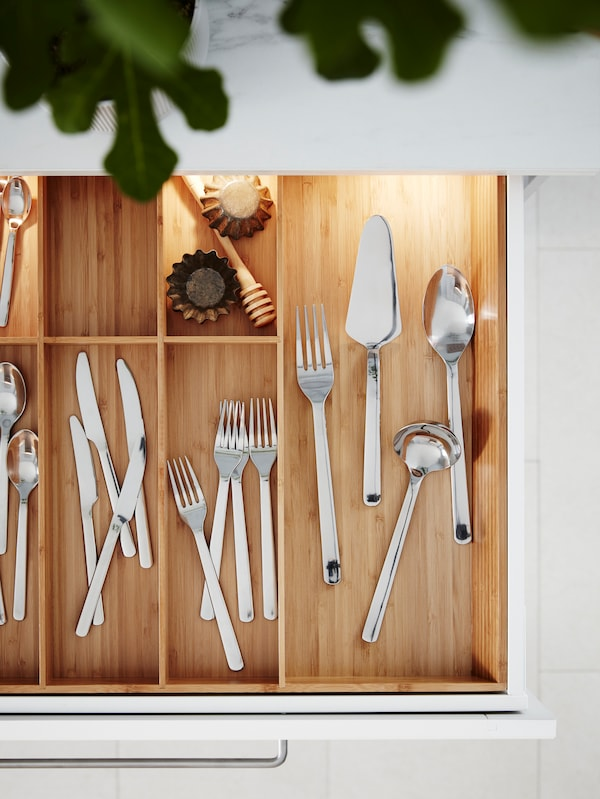 A kitchen drawer is pulled out revealing a VARIERA cutlery tray with cutlery in stainless-steel and baking accessories.