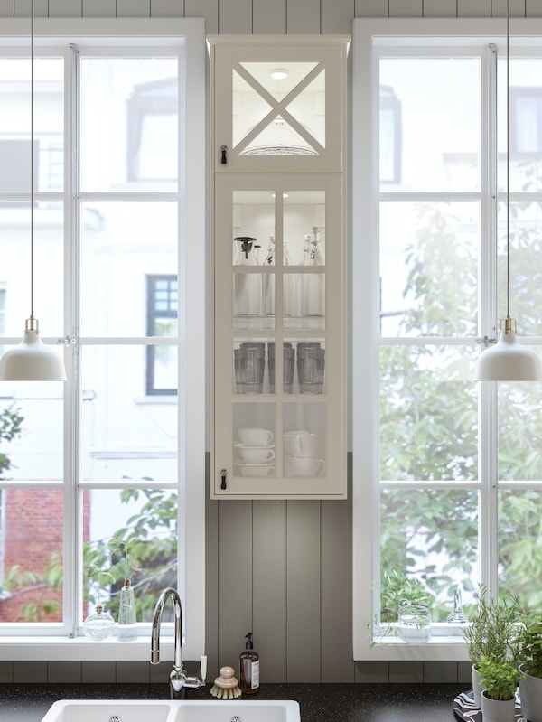An IKEA BODBYN white kitchen cabinet with vitrine glass doors between two narrow windows with two white pendant lamps.