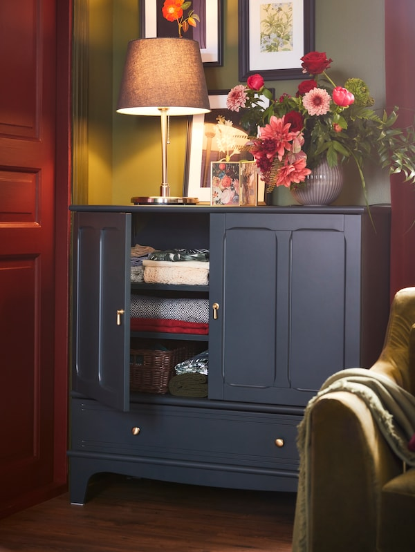 A dark blue-green cabinet with a table lamp and a vase with flowers on the top surface. Frames with flower motifs above.