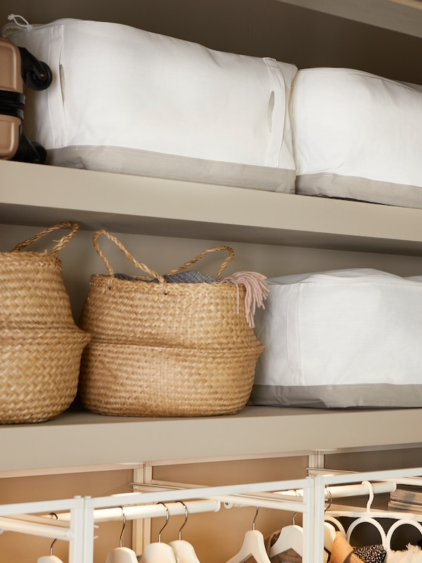 White LACKISAR storage cases and FLÅDIS baskets sit on shelves above the top part of a JONAXEL storage combination.