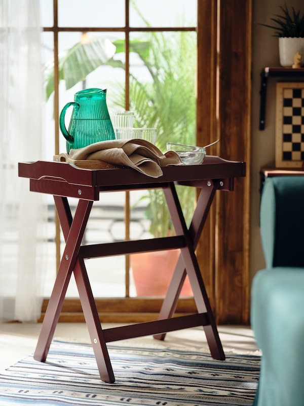 A green glass jug and other glassware placed on a dark-red MARYD tray table by a glass door leading to a patio with plants.