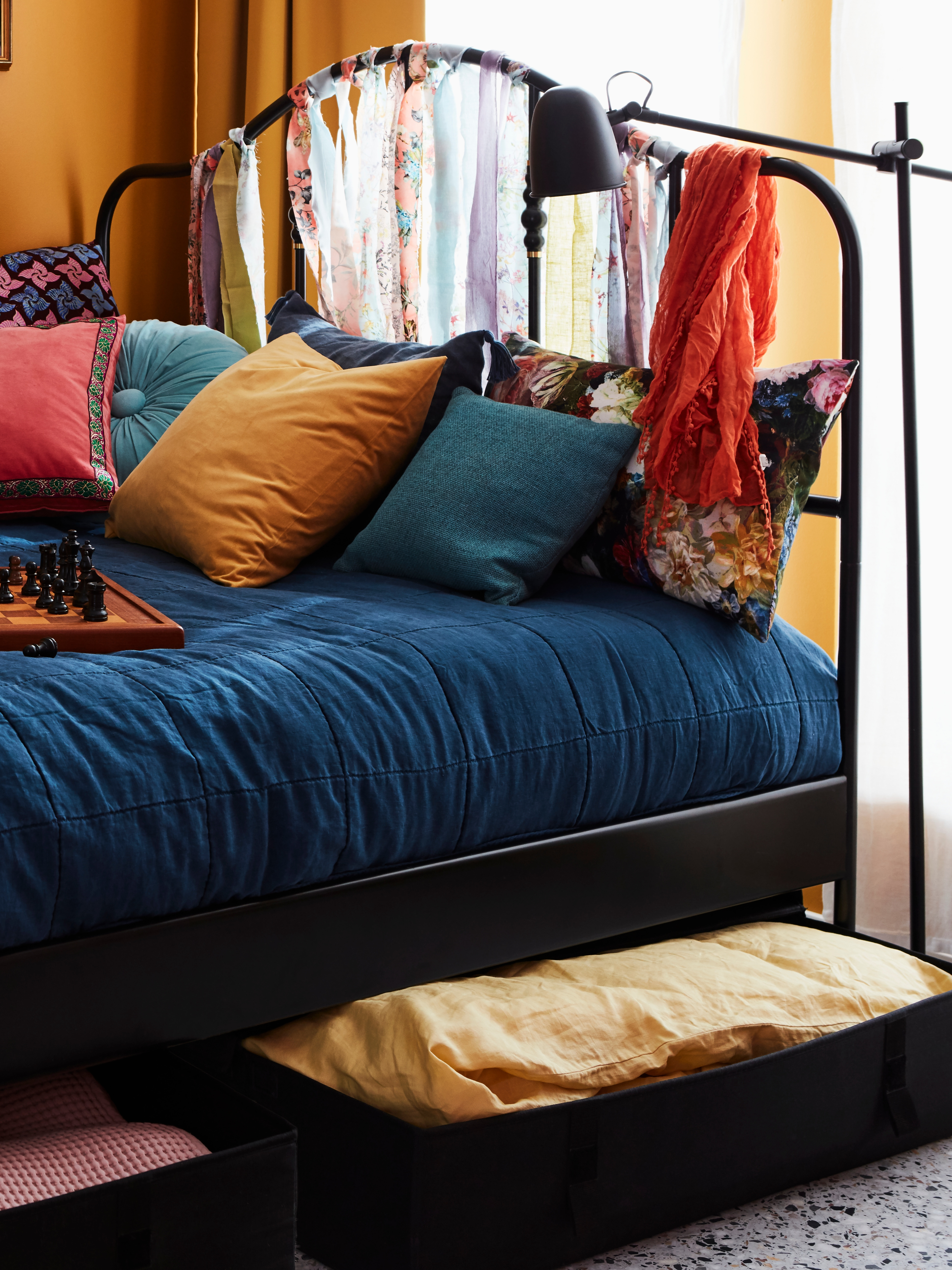A colourfully made bed with lots of cushions on a black-coated steel SAGSTUA bed frame has fabric storage cases underneath.
