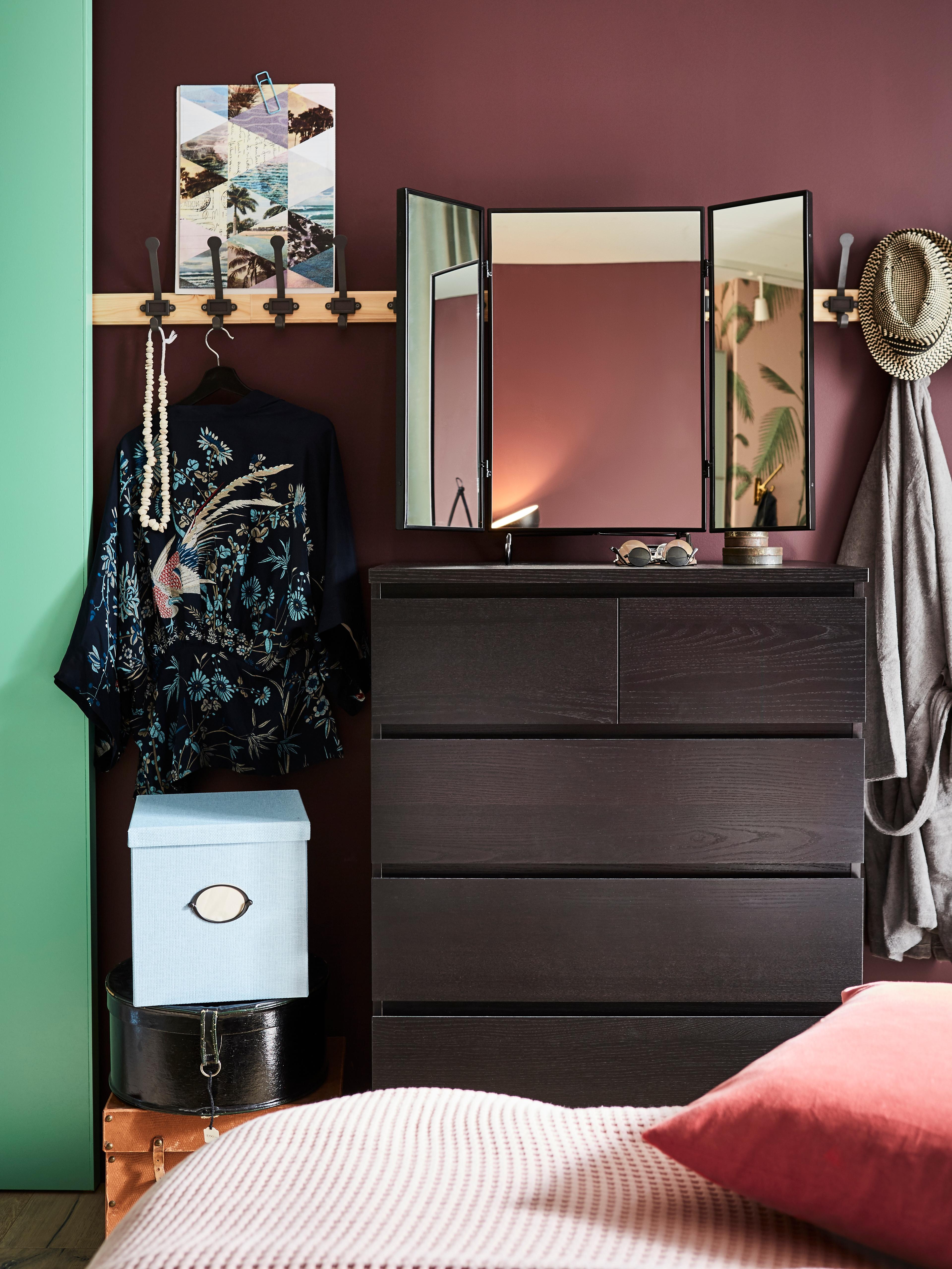 Camera da letto con cassettiera MALM su cui è appoggiato uno specchio, e binario a parete con vari oggetti appesi.