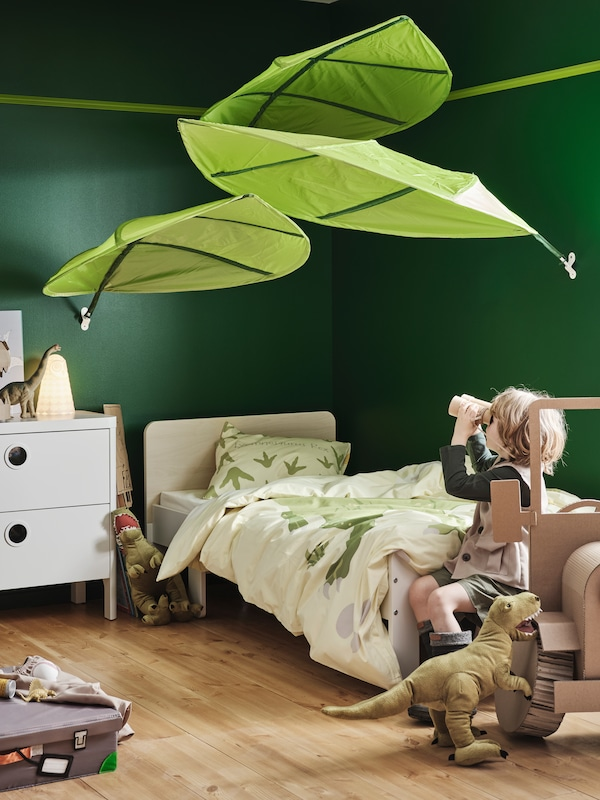A child sits on a SLÄKT extendable bed and looks through toy binoculars at three LÖVA bed canopies above the bed.