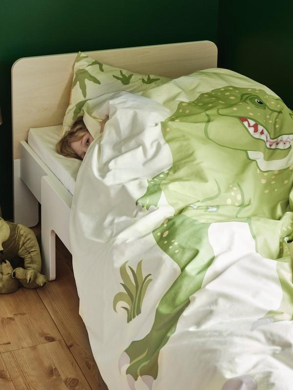 Dijete leži na SLÄKT produljivom krevetu s JÄTTELIK posteljinom s uzorcima dinosaura i viri ispod popluna.