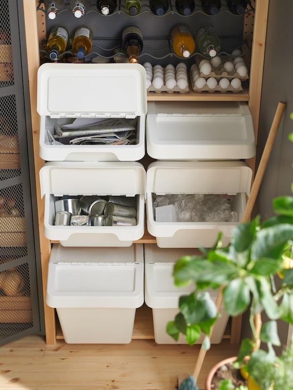 Forskellige sorteringsspande med hhv pap, metal og plast står stablet på hinanden i en IVAR reol