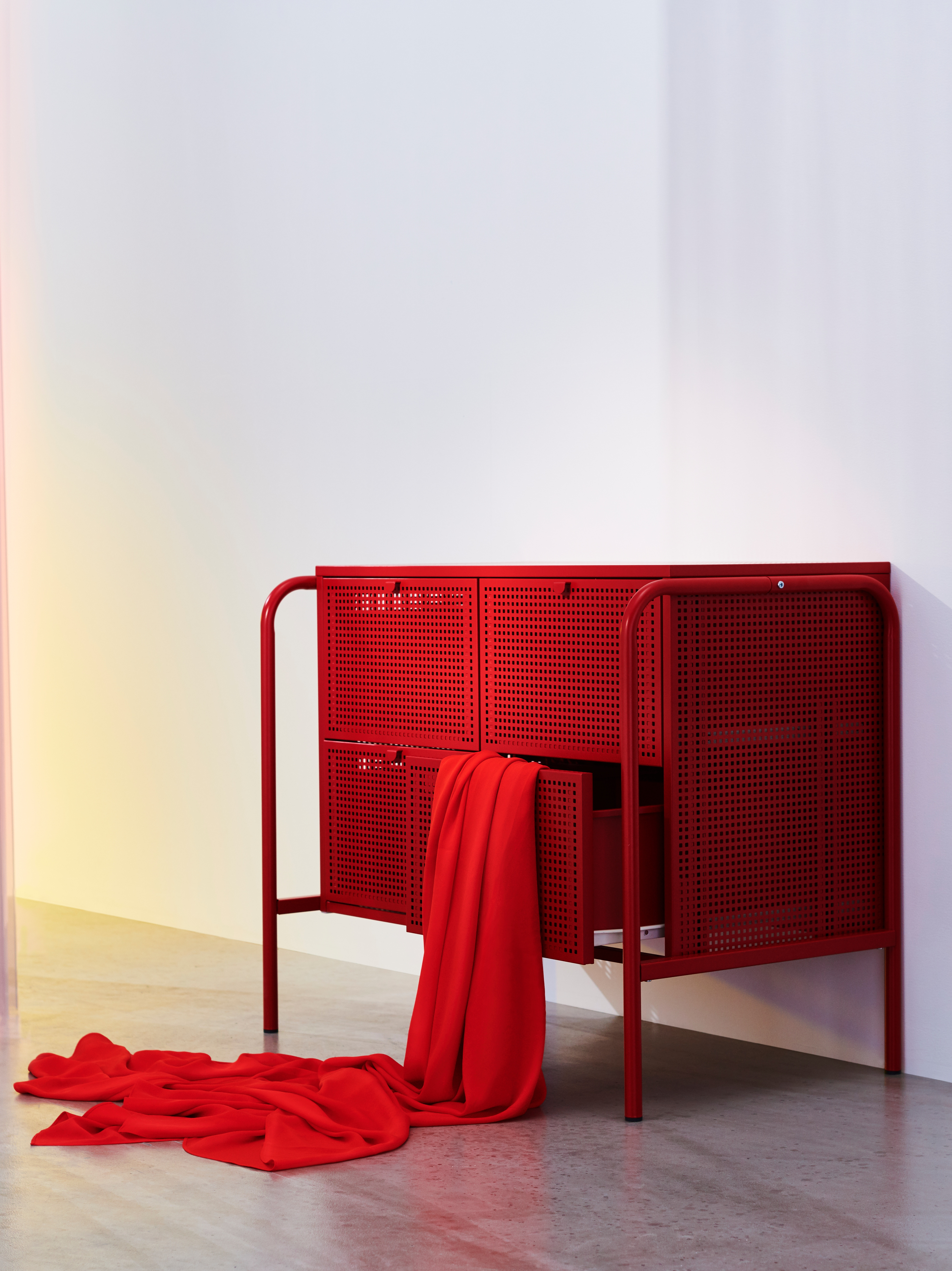 A red NIKKEBY chest of drawers in an industrial style with perforated metal, made for general storage.