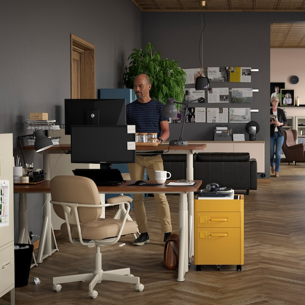 Dark coloured office. Man standing at sit/stand desk with yellow file cabinet beside him.