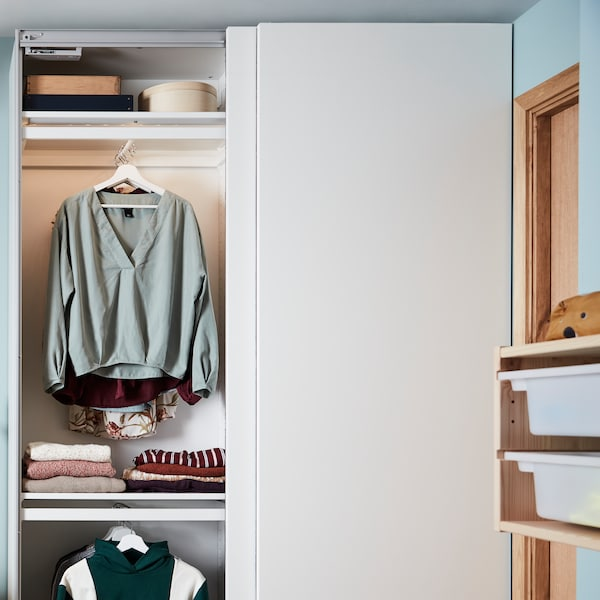 A PAX/HASVIK wardrobe combination with one sliding door open. There are folded and hanging clothes and boxes inside.