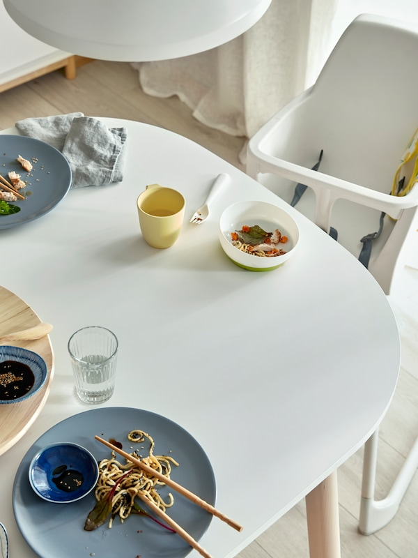 A young boy wearing a MATVRÅ bib sits in a highchair at a table with HEROISK bowls, plates, a mug and cutlery.