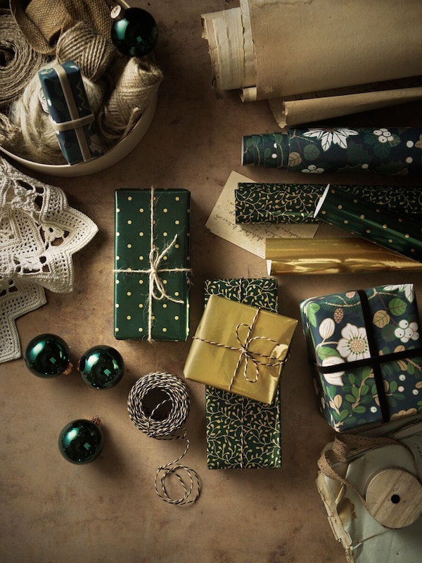Superficie de trabajo con muchos regalos envueltos junto con papel de regalo, una cuerda, cinta, bolas de Navidad y otros artículos.