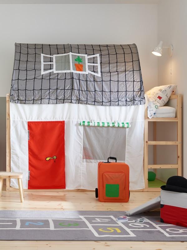 Un lit haut/bas KURA dans une chambre d'enfant avec une tente de lit avec rideau KURA. Une valise orange et un tapis gris au sol.