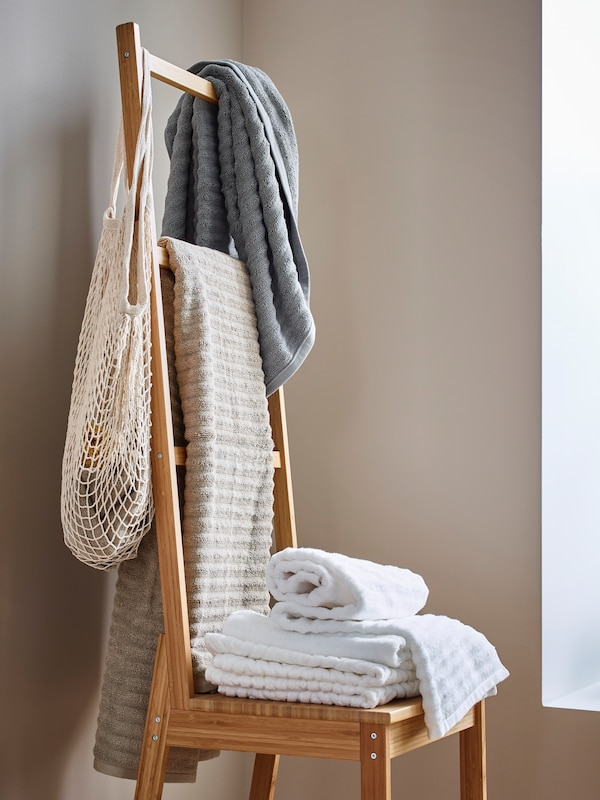 A RÅGRUND towel rack chair with towels and a mesh bag hanging from the back and folded towels on the seat.