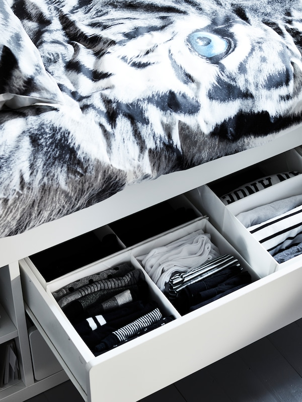 A white SLÄKT bed with storage with one drawer open containing folded clothes in RASSLA boxes with compartments.