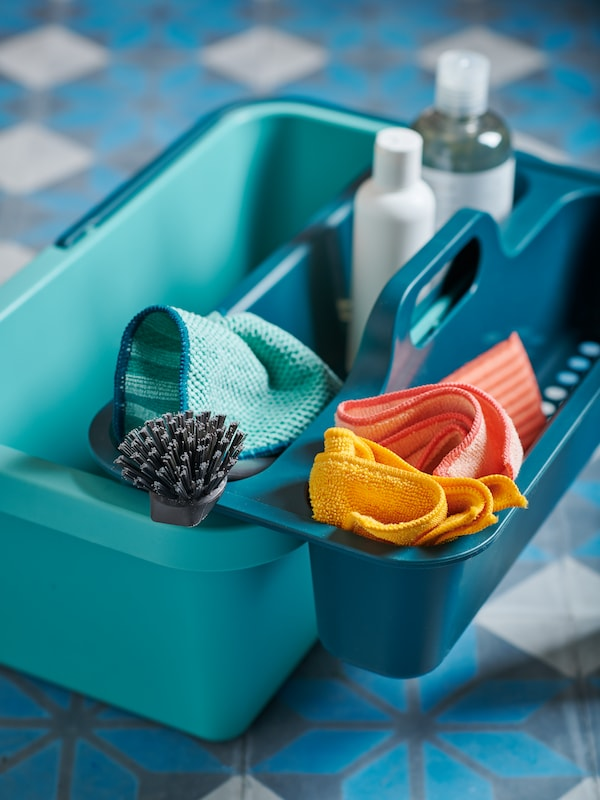 A PEPPRIG cleaning bucket with its caddy, filled with cleaning accessories, straddling one of the bucket's sides.